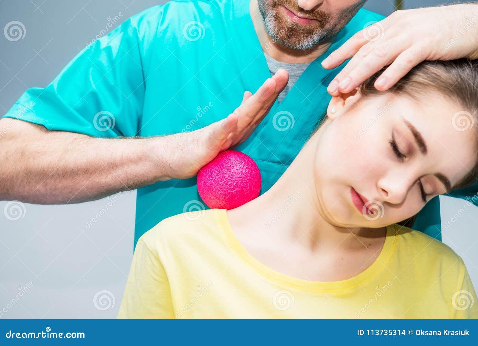 A mulher na fisioterapia que recebe a massagem da bola do quiroprático do terapeuta A trata o ombro paciente do ` s, pescoço em o