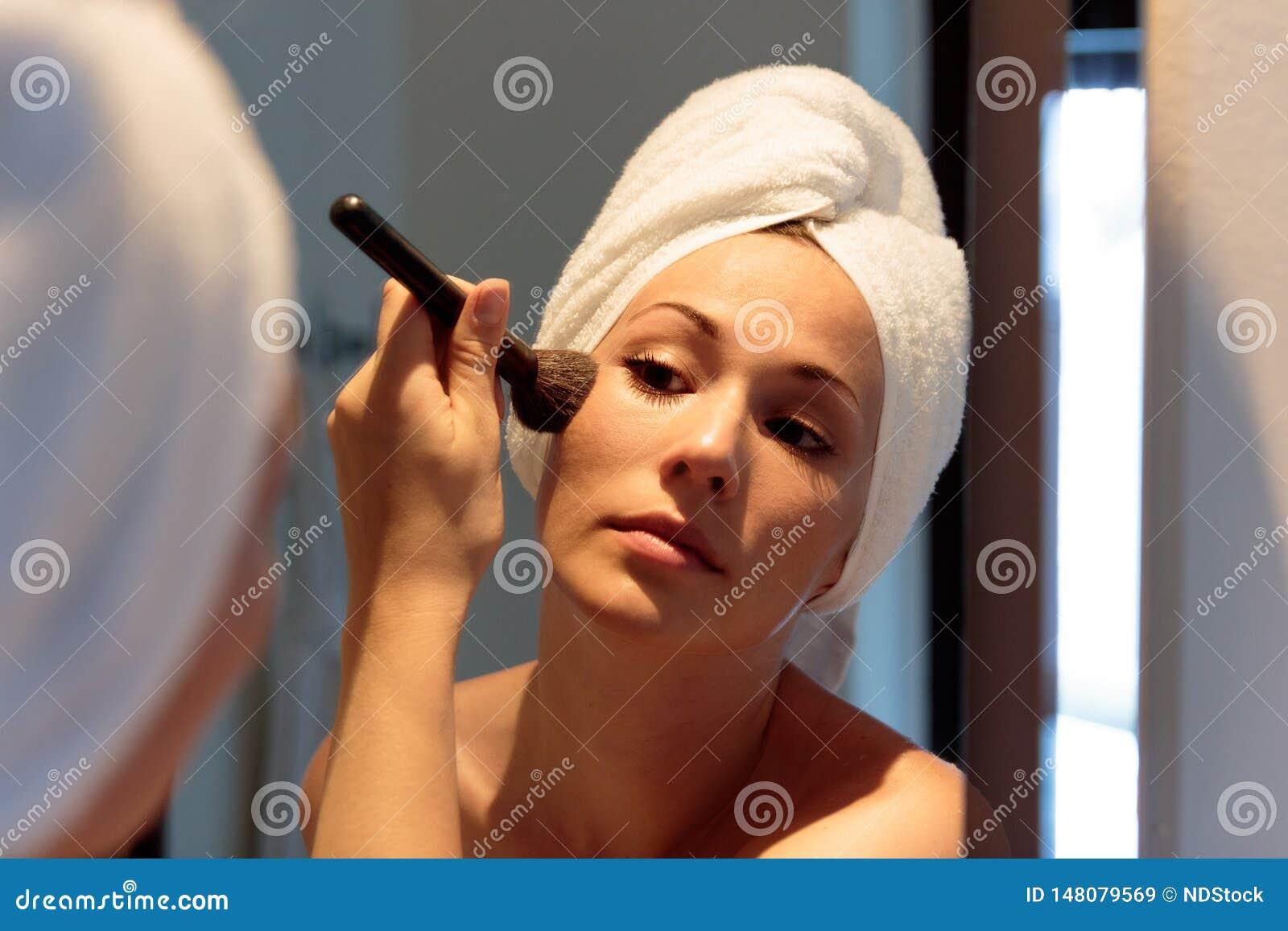 Mulher na frente do espelho que está pondo sobre a composição antes de sair na noite