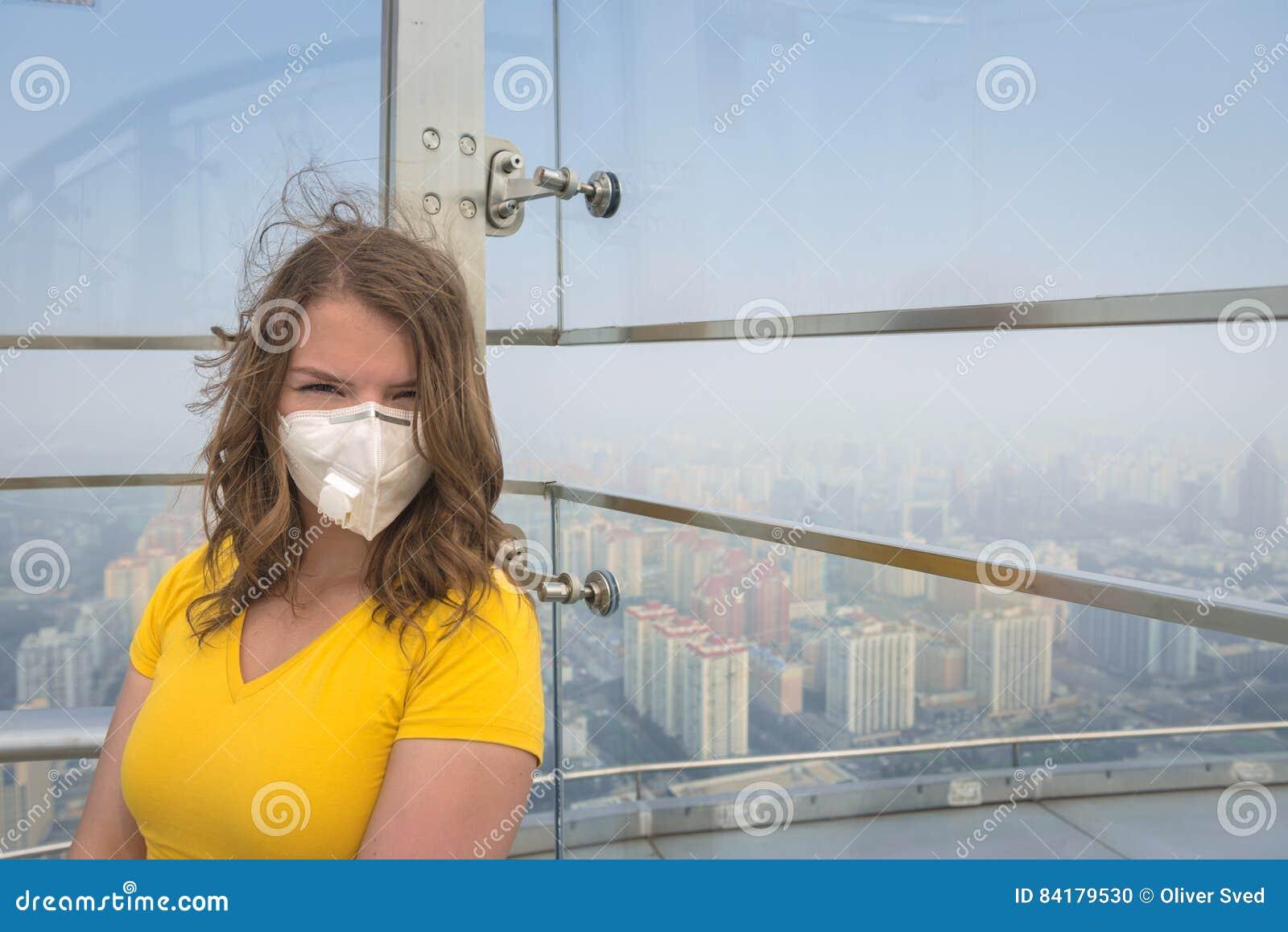 Mulher na máscara médica contra a poluição do ar