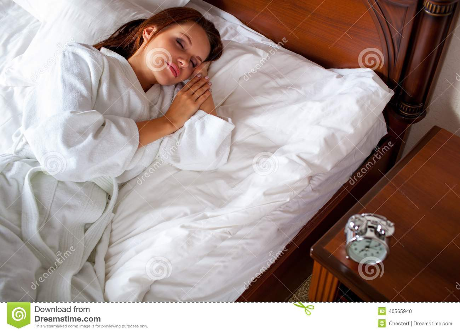 Mulher na mão de alargamento da cama ao despertador