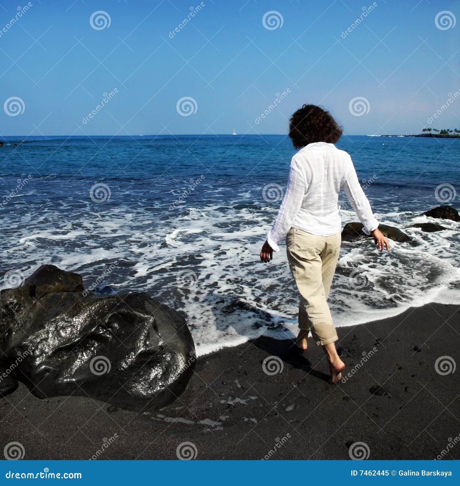 Mulher na praia preta da areia
