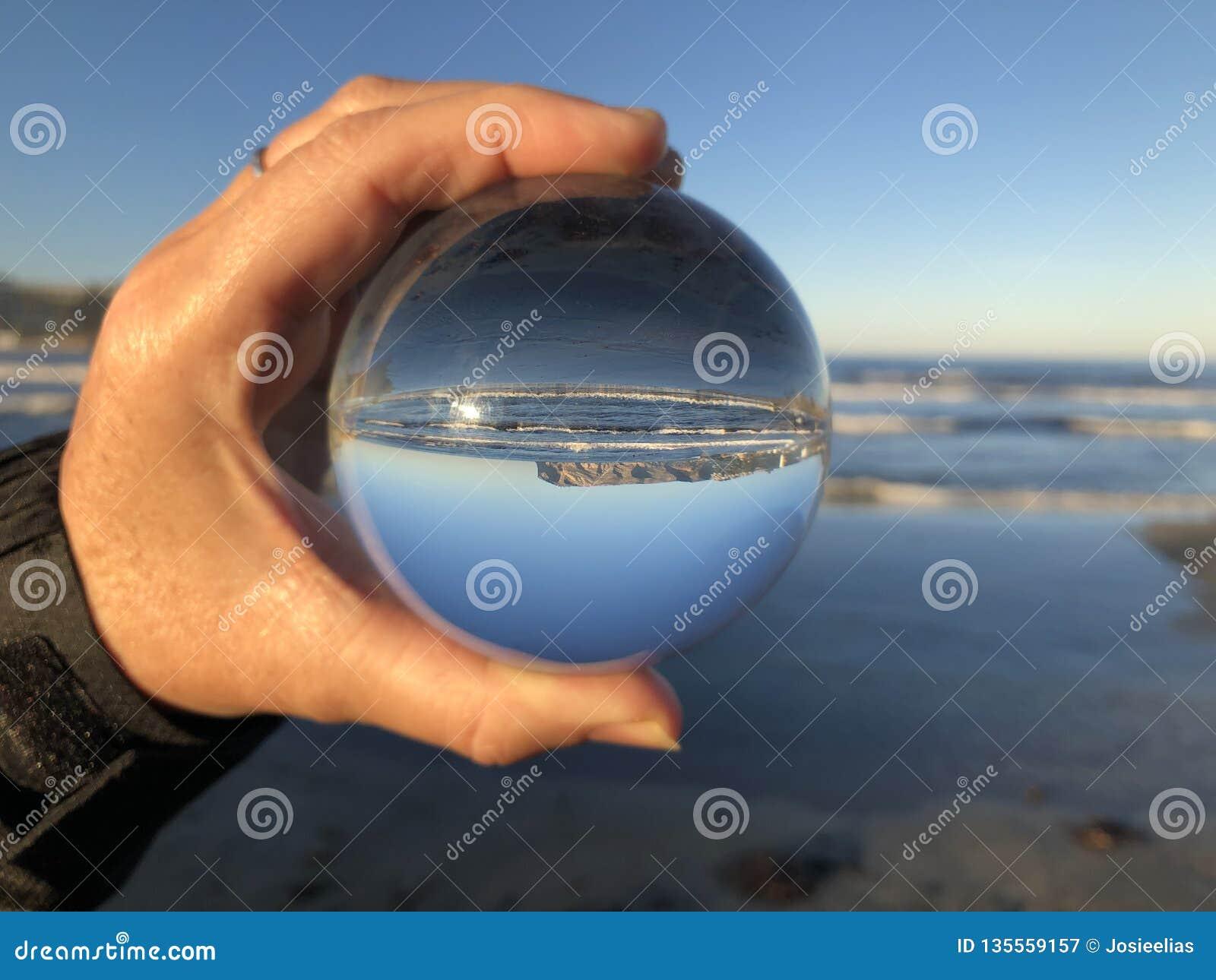 Mulher na praia que guarda uma bola de cristal