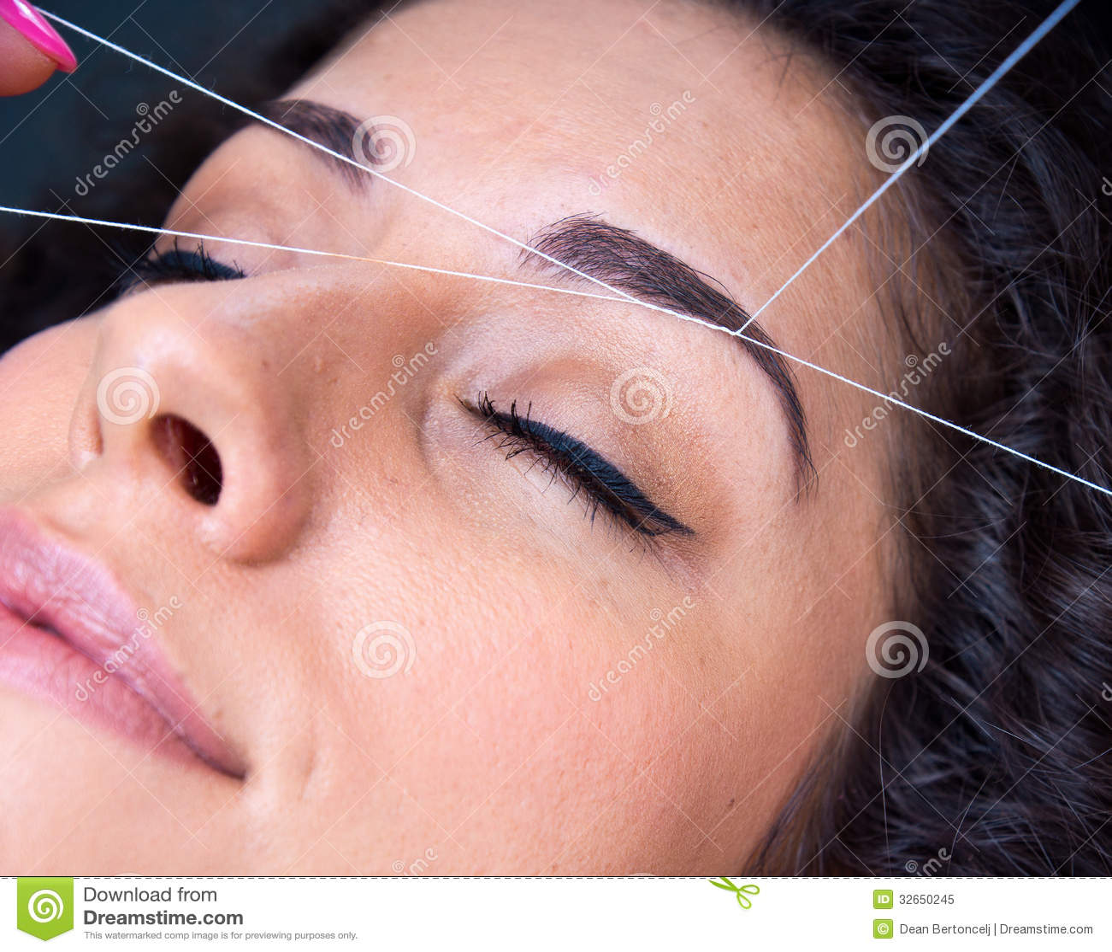Mulher na remoção dos pêlos faciais que rosqueia o procedimento