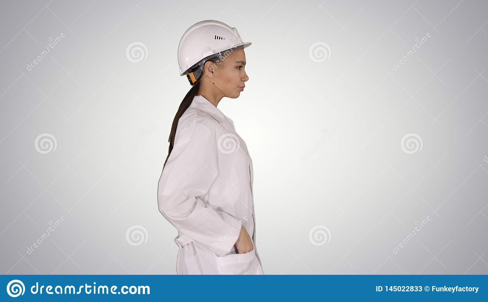 Mulher na veste branca que p?e o capacete de seguran?a sobre ao andar sobre o fundo do inclina??o