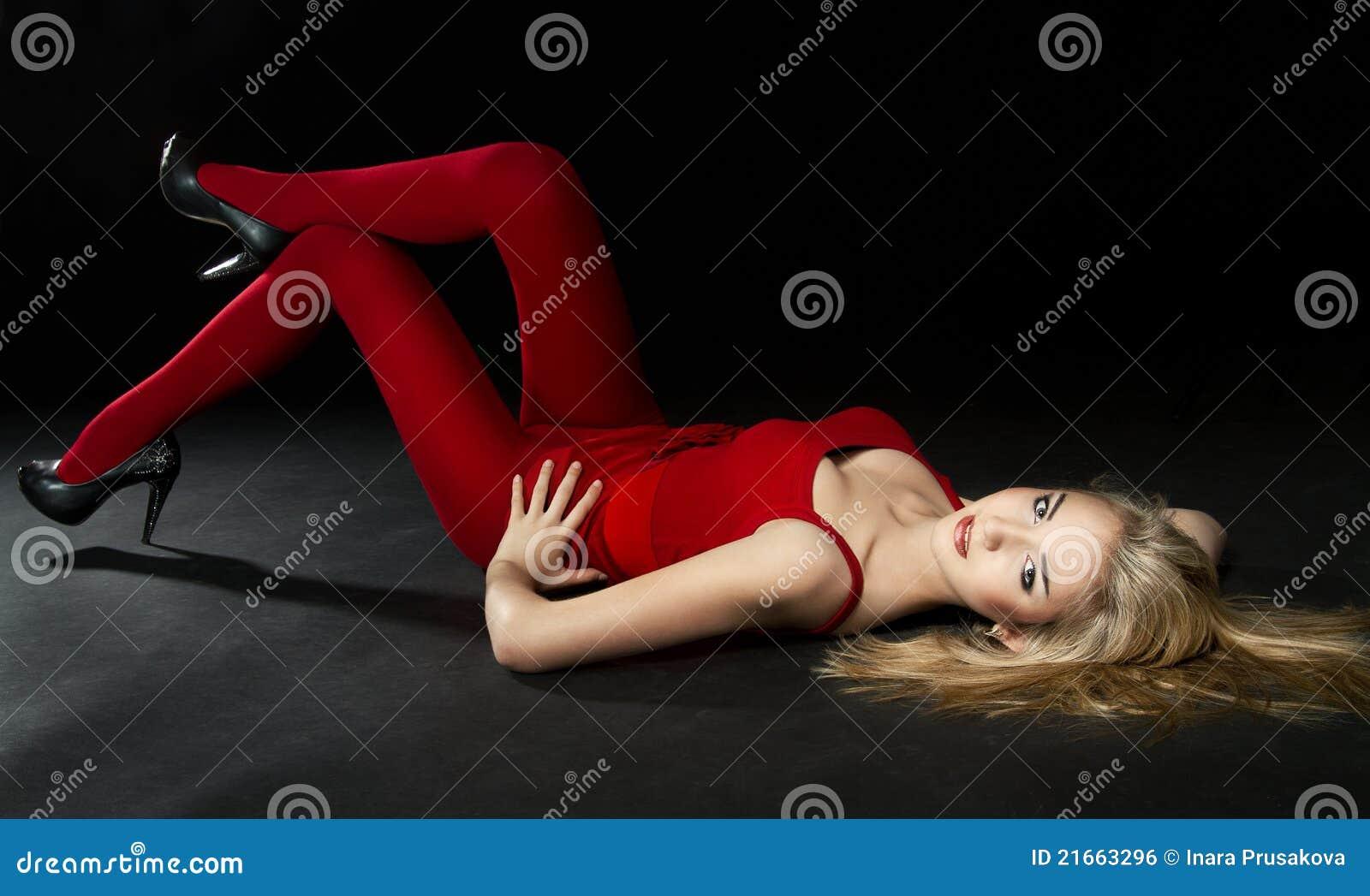 Mulher nas calças justas vermelhas que encontram-se para baixo. Sobre o fundo