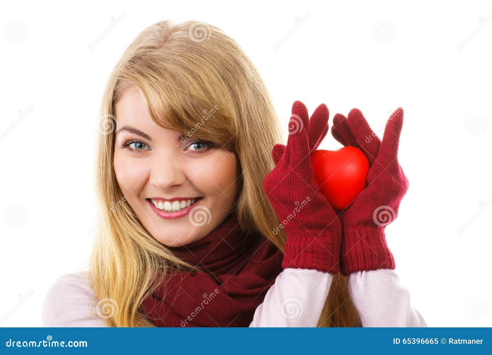 Mulher nas luvas de lã que guardam o coração vermelho, símbolo do amor
