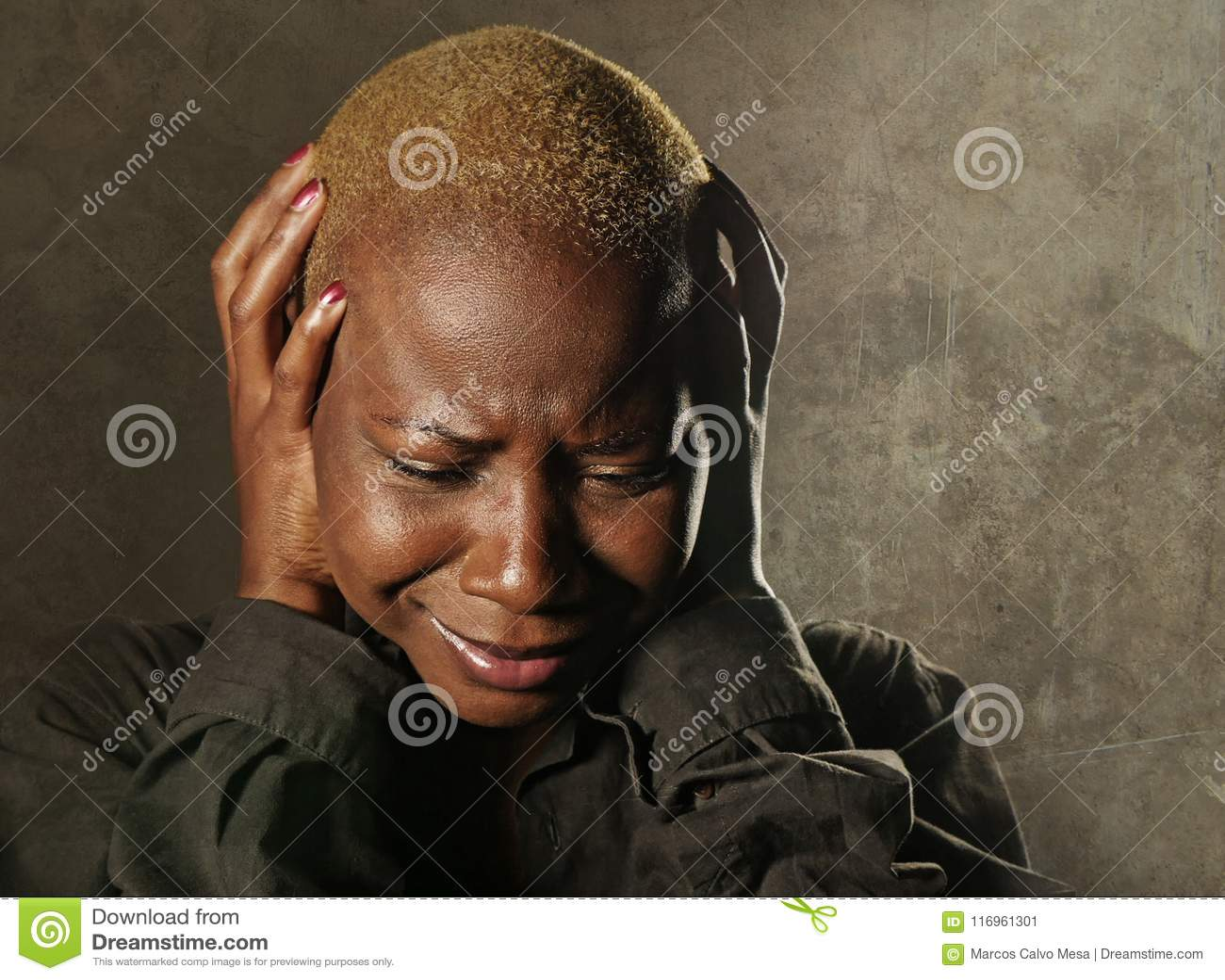 Mulher negra afro-americana triste e deprimida à moda nova que grita no desespero que guarda principal com as mãos que sentem mis
