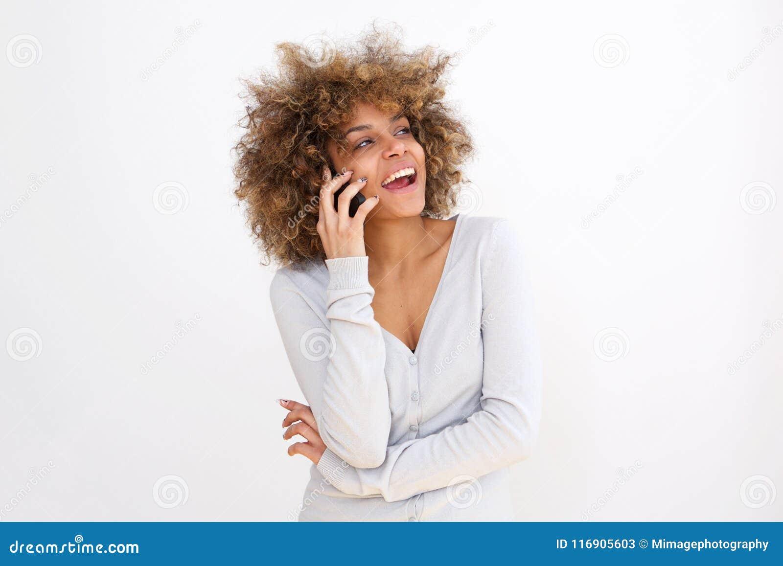 Mulher negra nova bonita que fala no telefone celular contra o fundo do whit