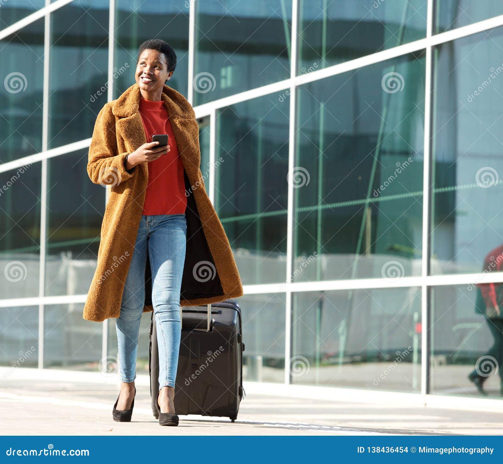 Mulher negra nova do corpo completo que anda fora com bagagem e telefone celular