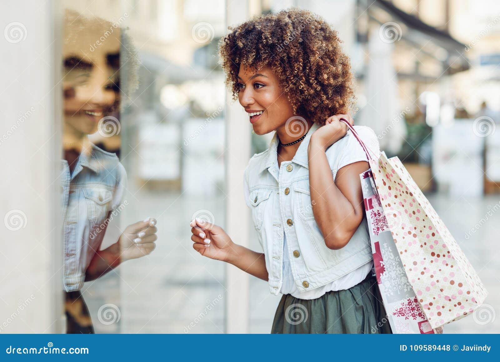 Mulher negra nova, penteado afro, olhando uma janela da loja