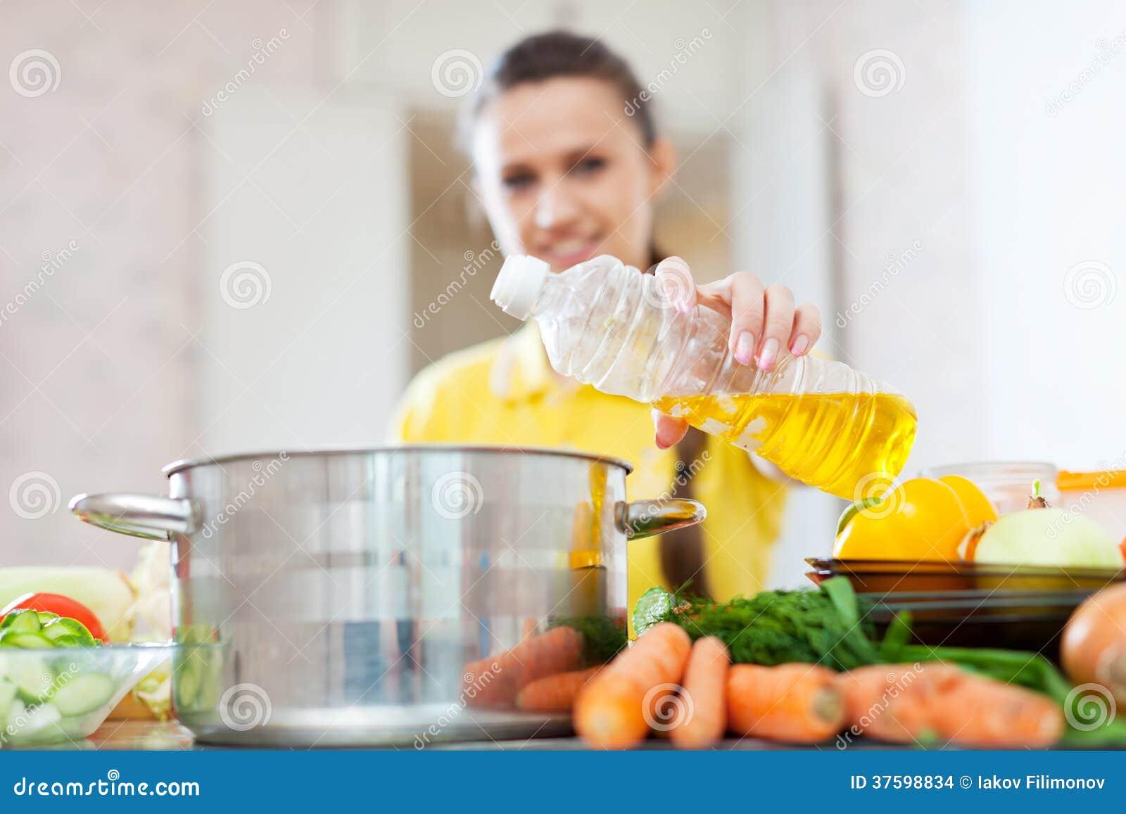 A mulher no amarelo derrama o óleo da garrafa