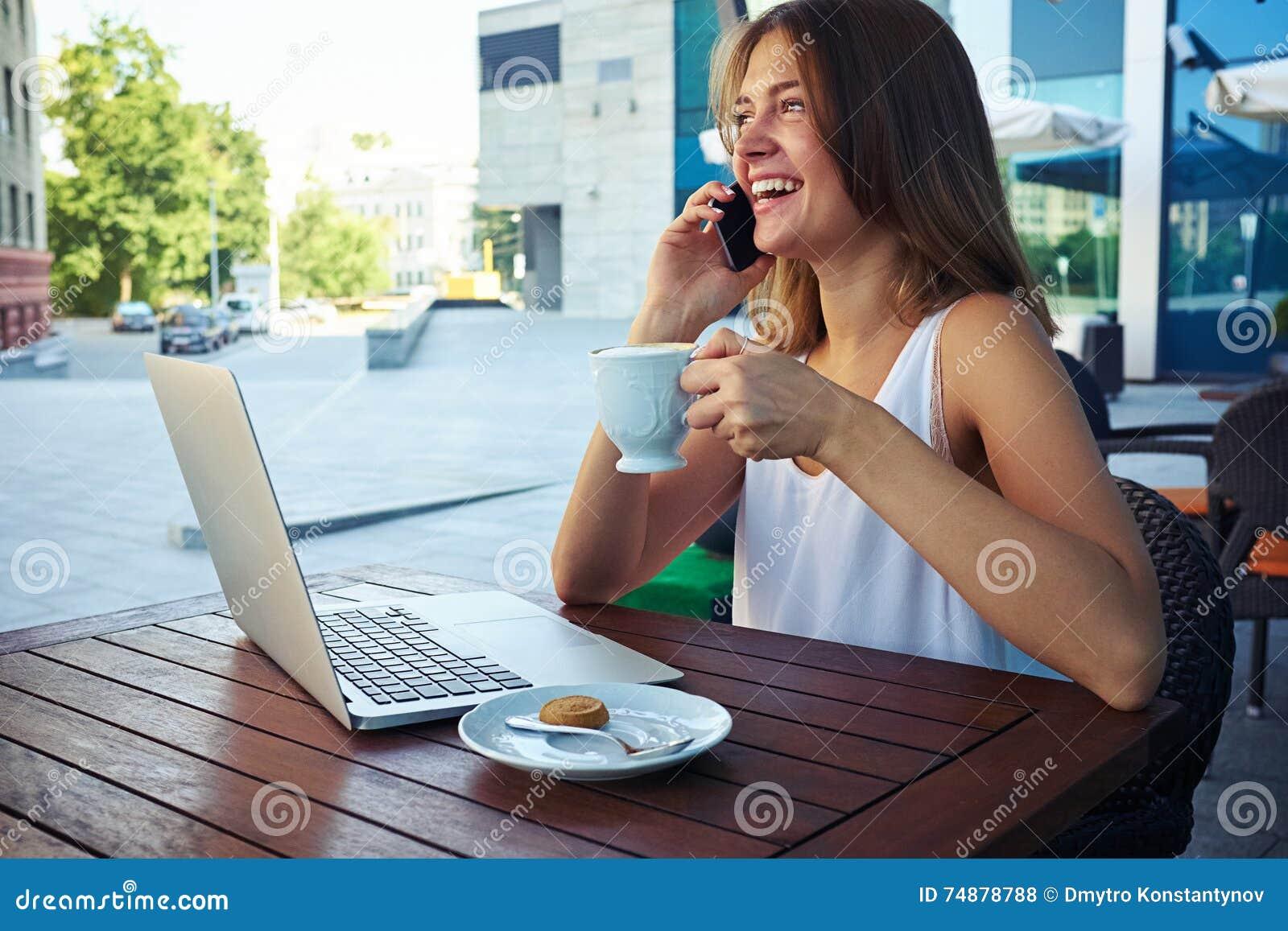 Mulher no café bebendo do café exterior ao falar no phon