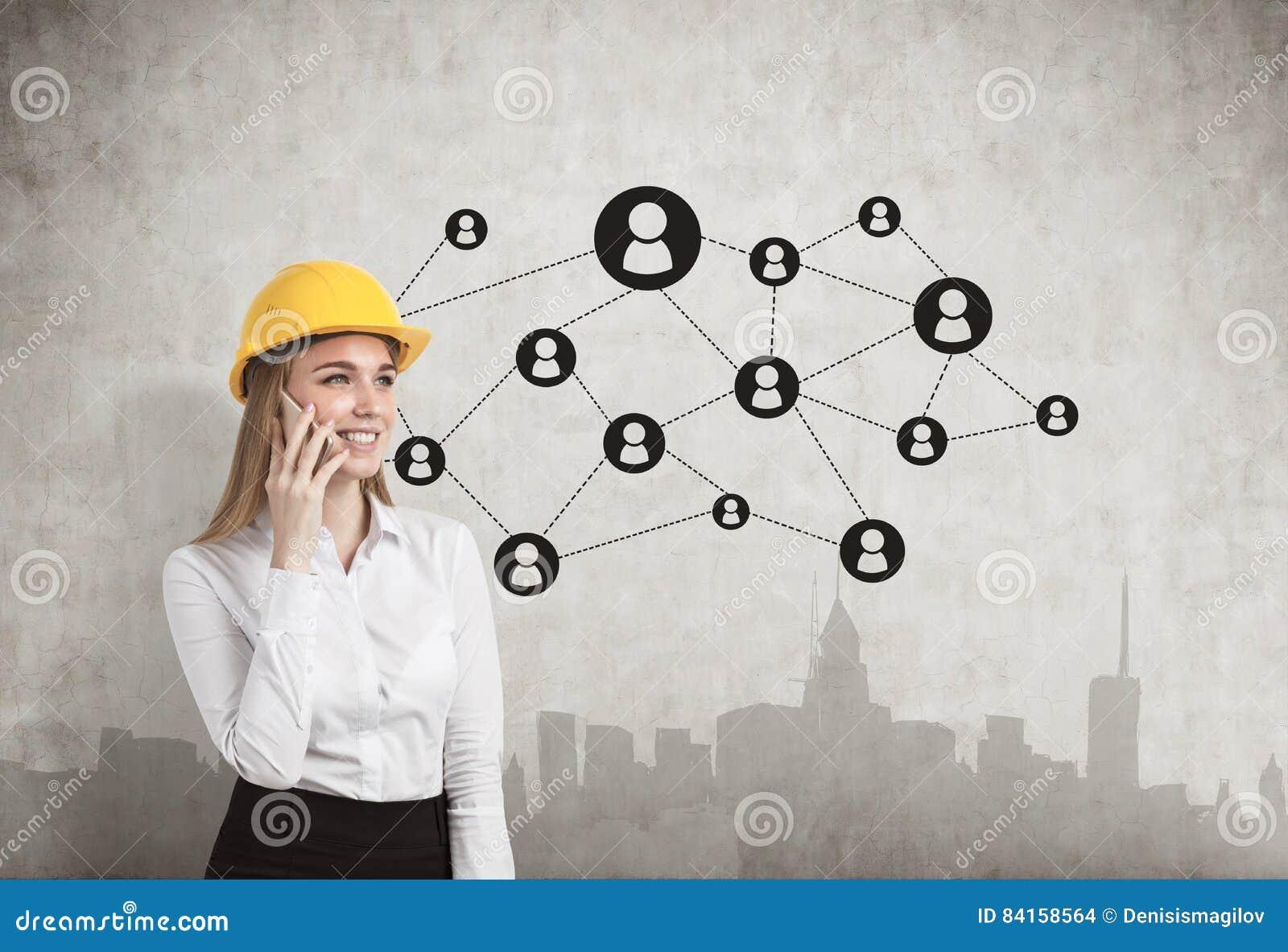 Mulher no capacete de segurança, muro de cimento, rede, cidade