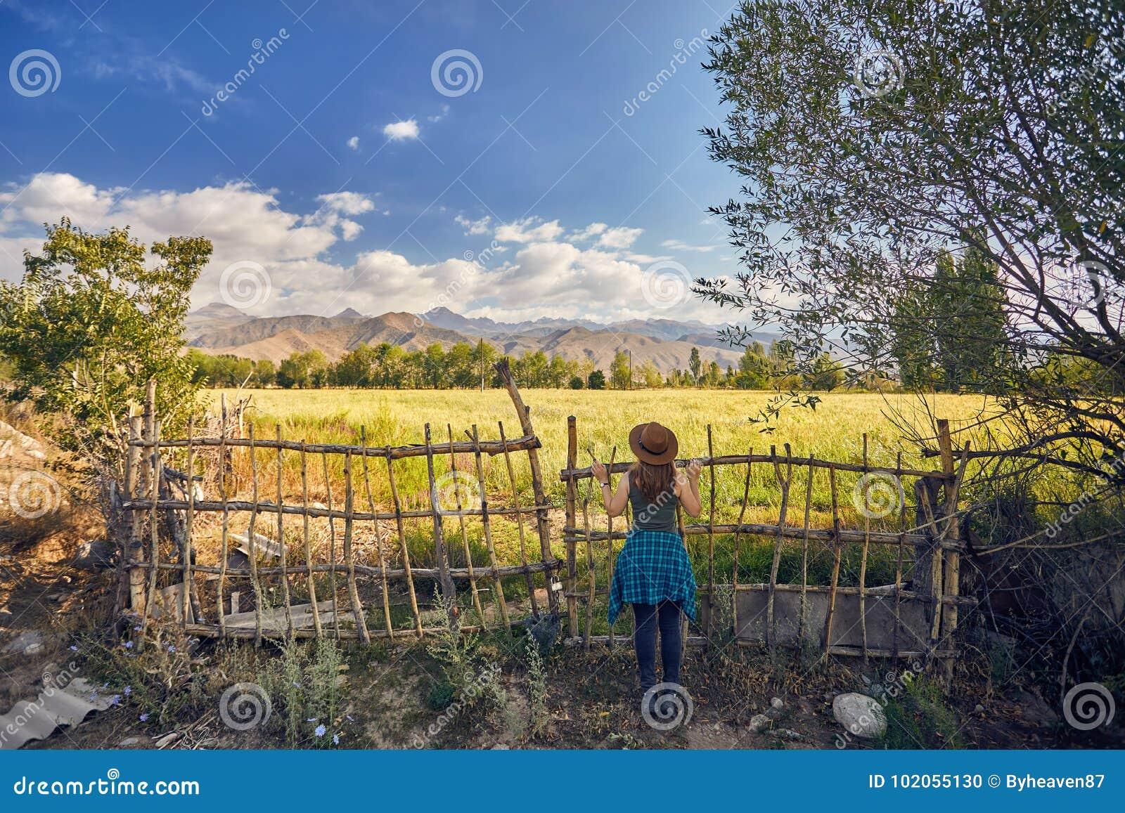 Mulher no chapéu no campo no por do sol