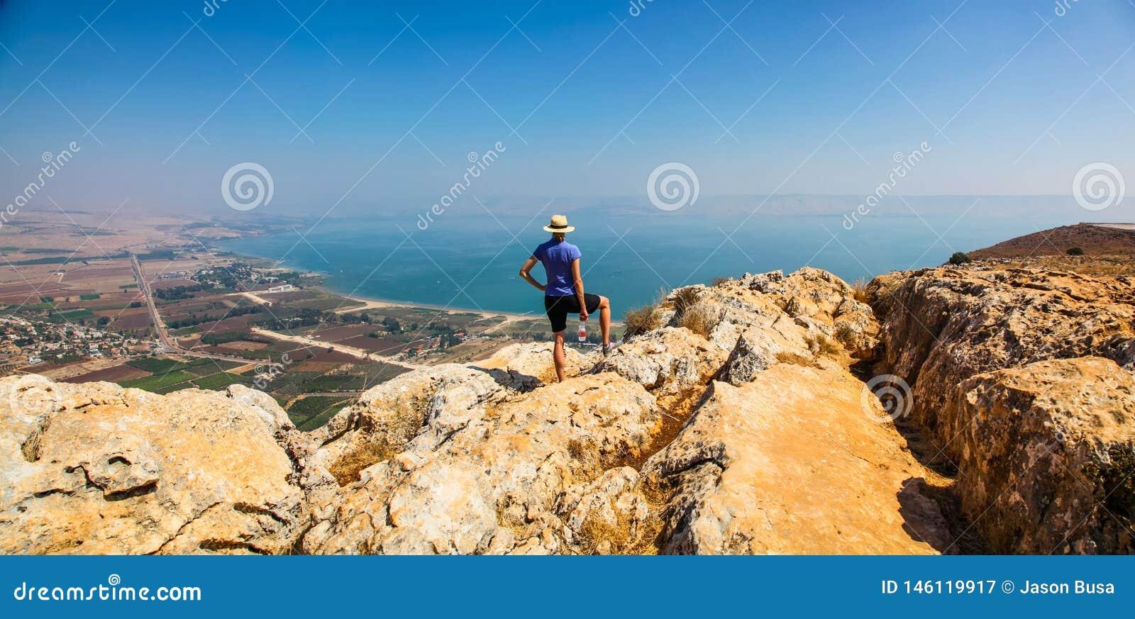 Mulher no chapéu que aprecia a vista panorâmica do mar de Galilee