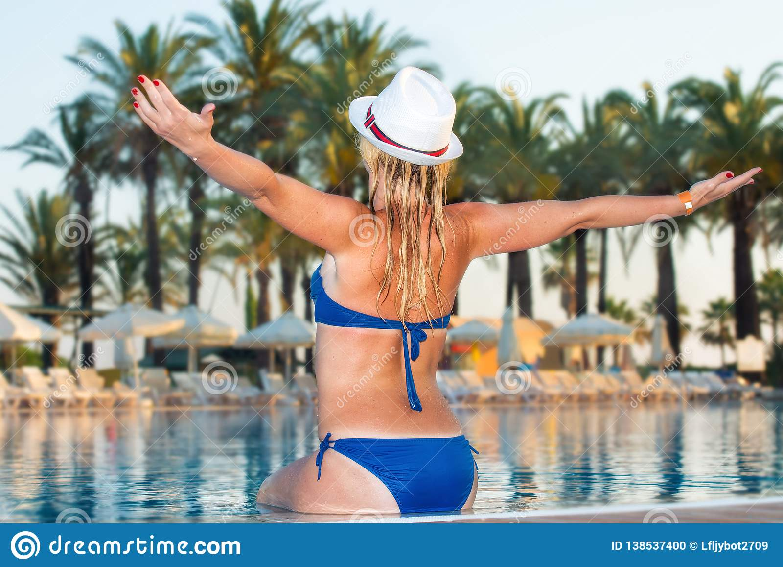 Mulher no chapéu que relaxa na piscina Menina na associação do spa resort do curso Férias do luxo do verão