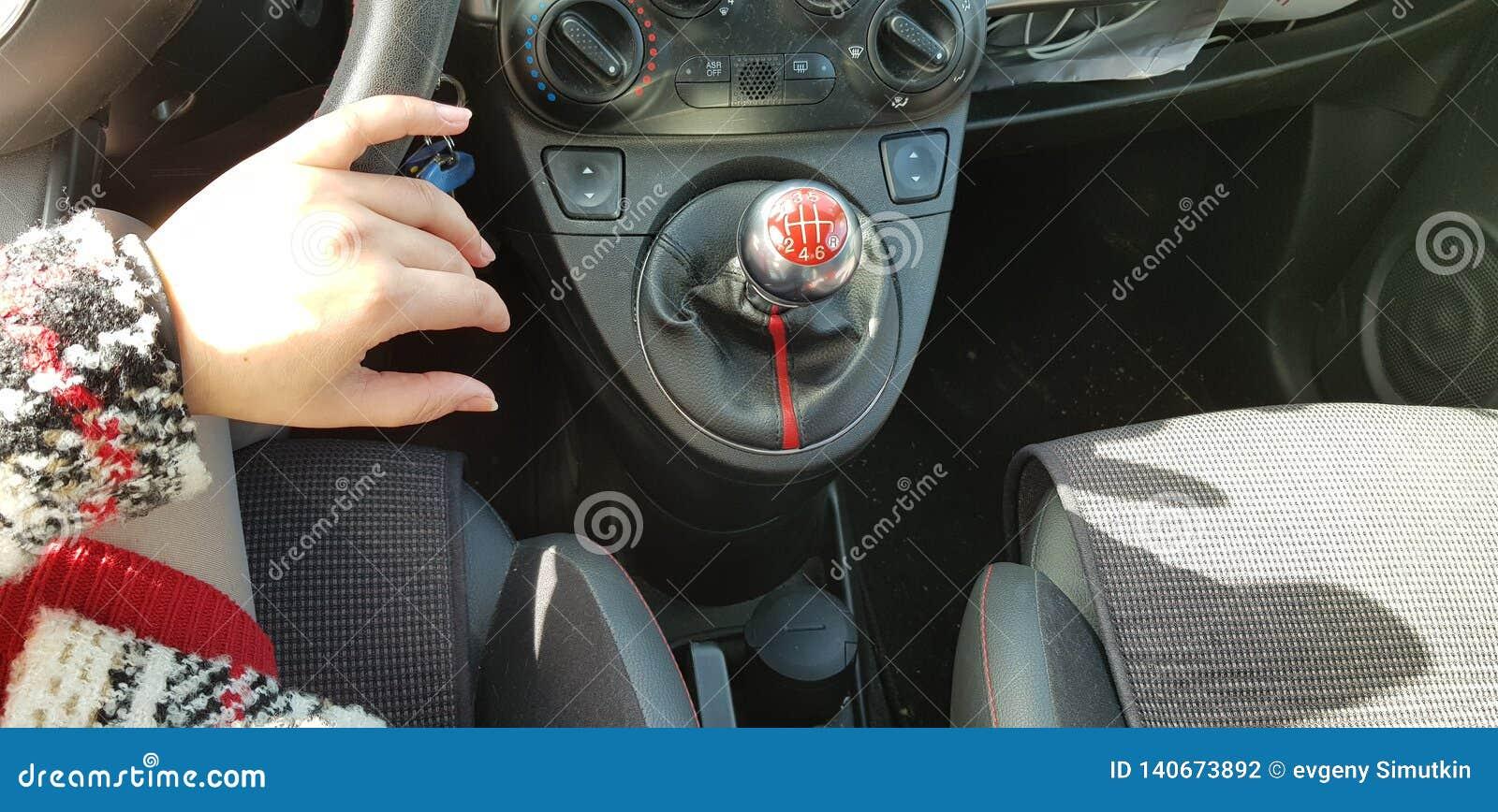 Mulher no mini vestido vermelho que senta no assento de motoristas sua mão no volante