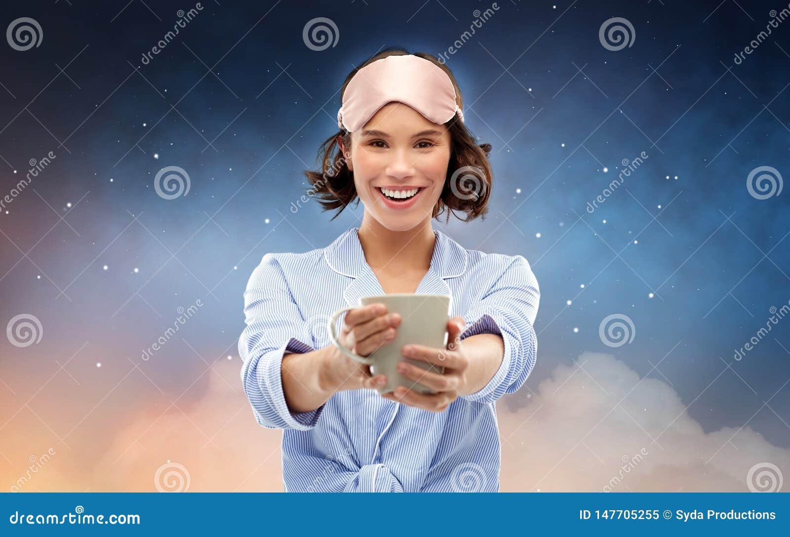 Mulher no pijama e no caf? bebendo da m?scara do sono