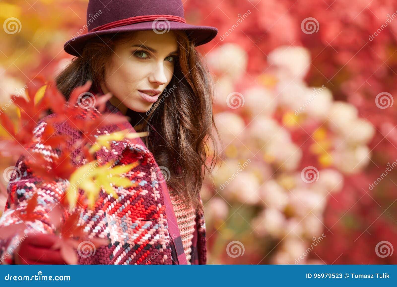 A mulher no revestimento com chapéu e o lenço no outono estacionam