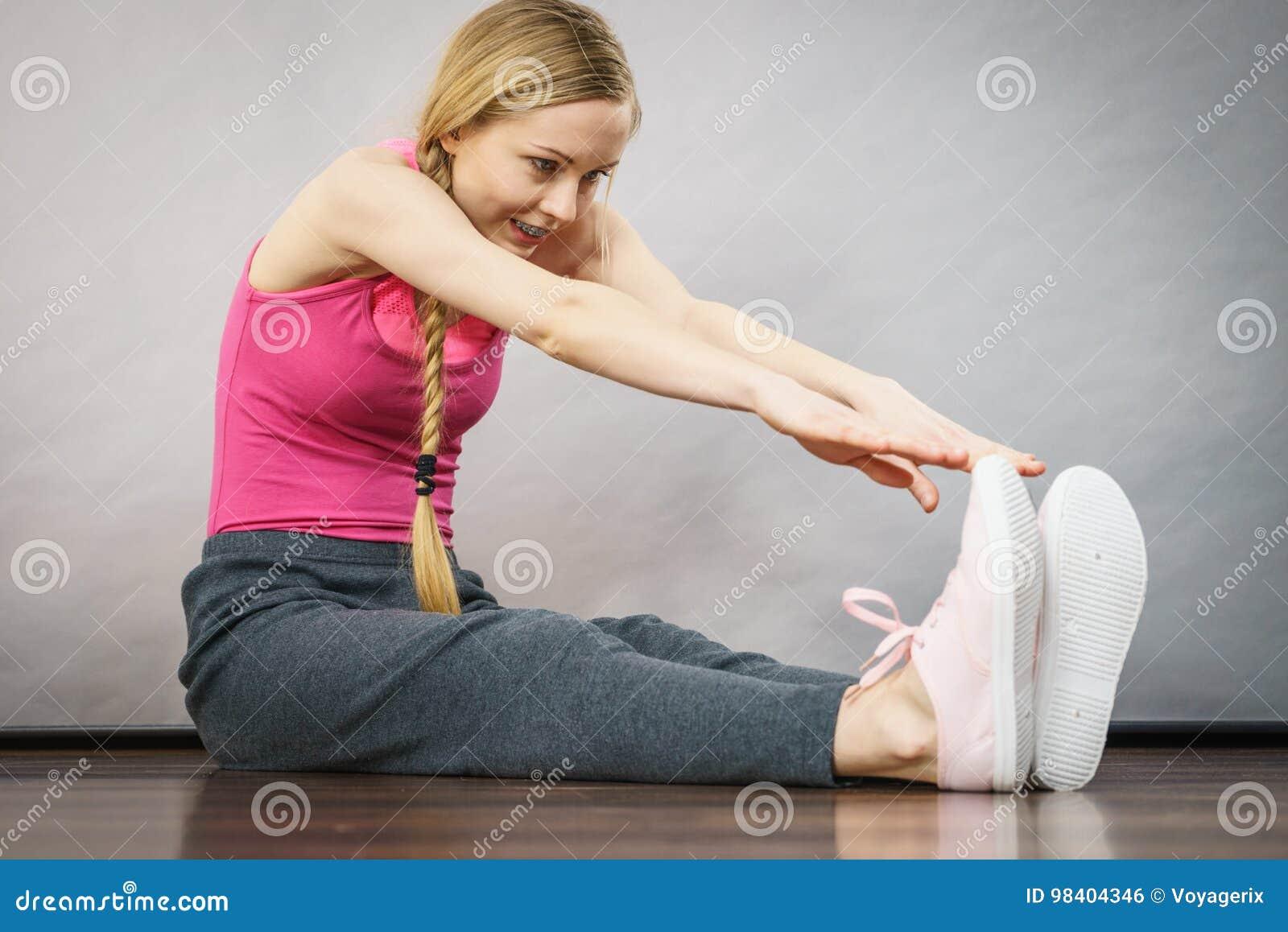 Mulher no sportswear que estica os pés