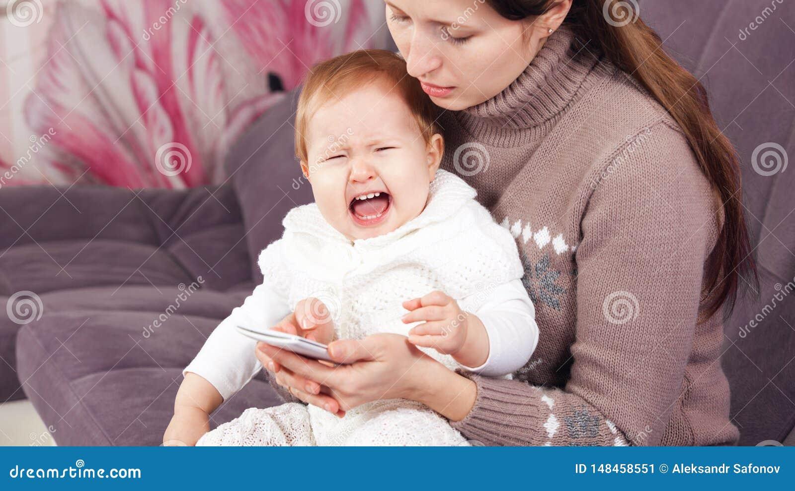 A mulher no telefone, ignora a criança de grito