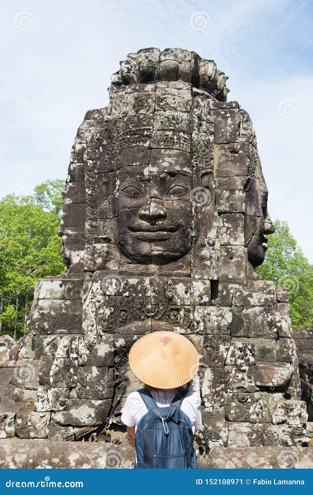 Mulher no templo de Bayon que olha as caras de pedra, Angkor Thom, c?u azul claro da luz da manh? Conceito da medita??o do budism