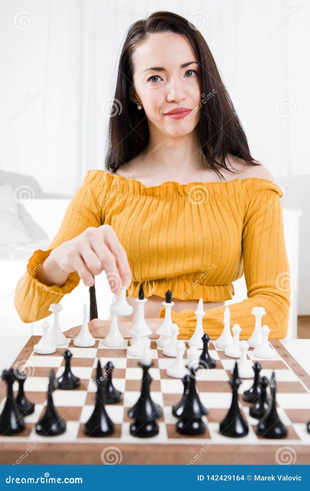 Mulher no vestido amarelo que senta-se na frente da xadrez - seu movimento