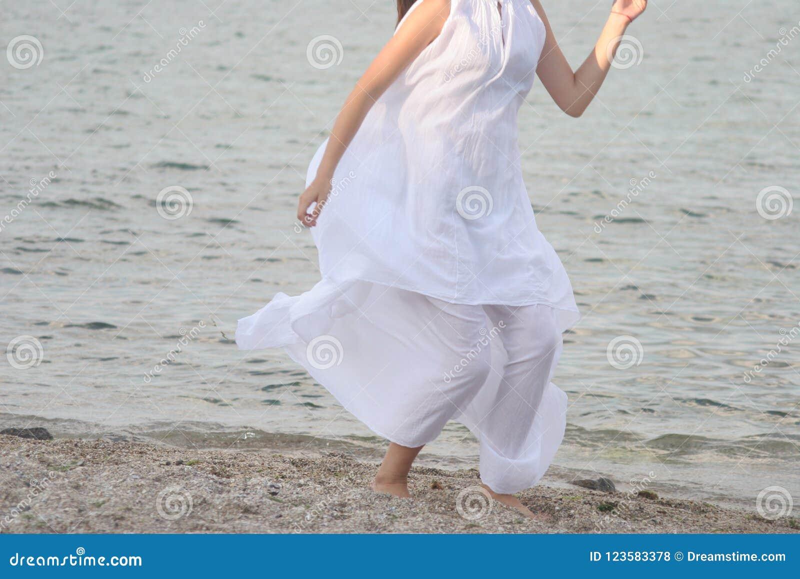 A mulher no vestido branco corre ao longo do Sandy Beach