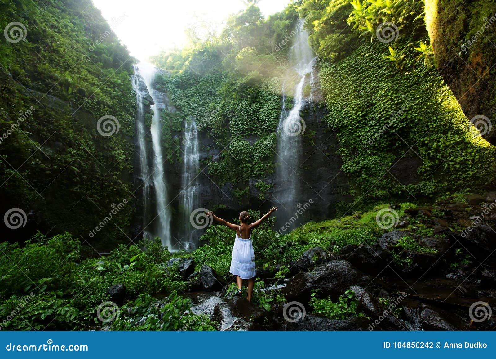 Mulher no vestido branco nas cachoeiras de Sekumpul nas selvas em vagabundos