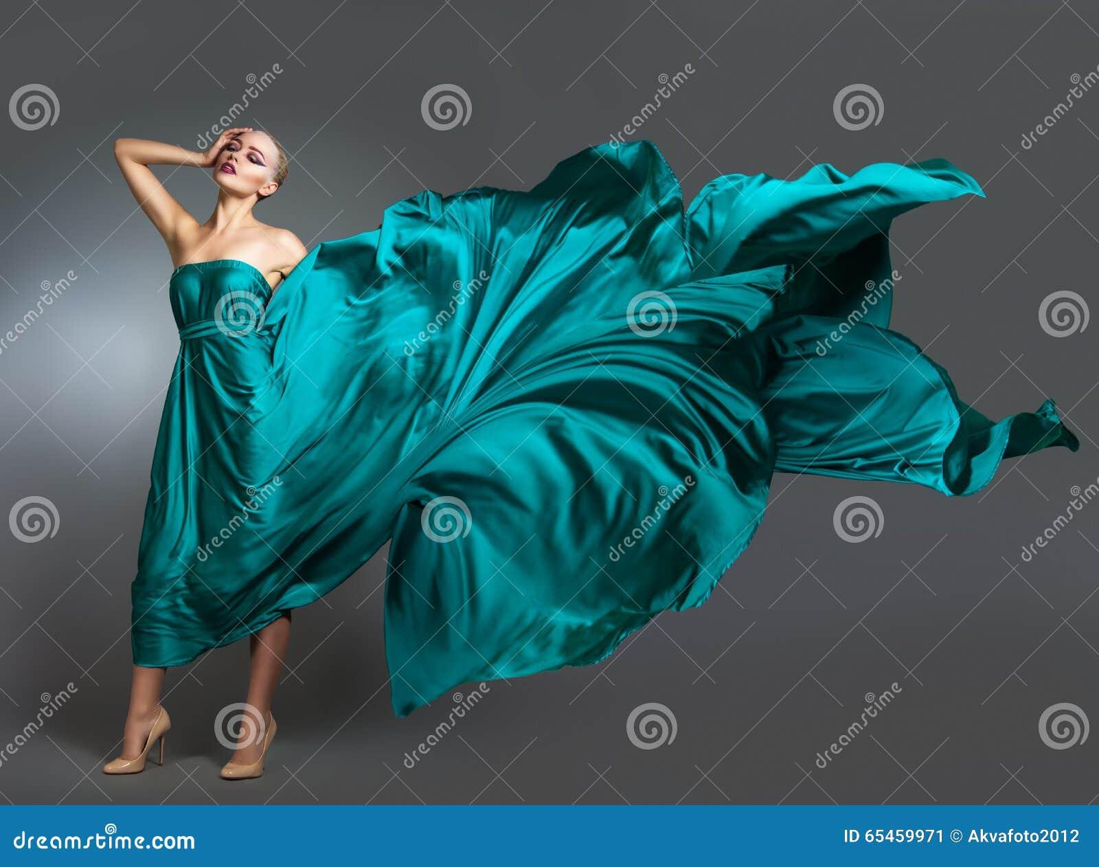 Mulher no vestido de seda que acena no vento Pano de voo e de vibração do vestido sobre o fundo cinzento