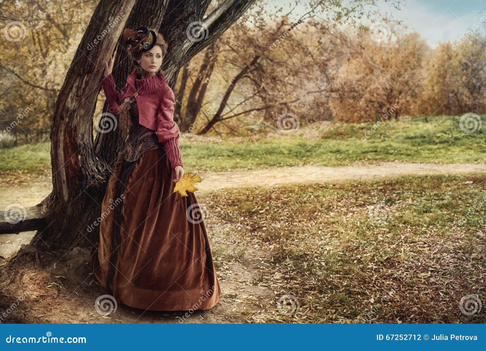 Mulher no vestido histórico perto da árvore na floresta do outono