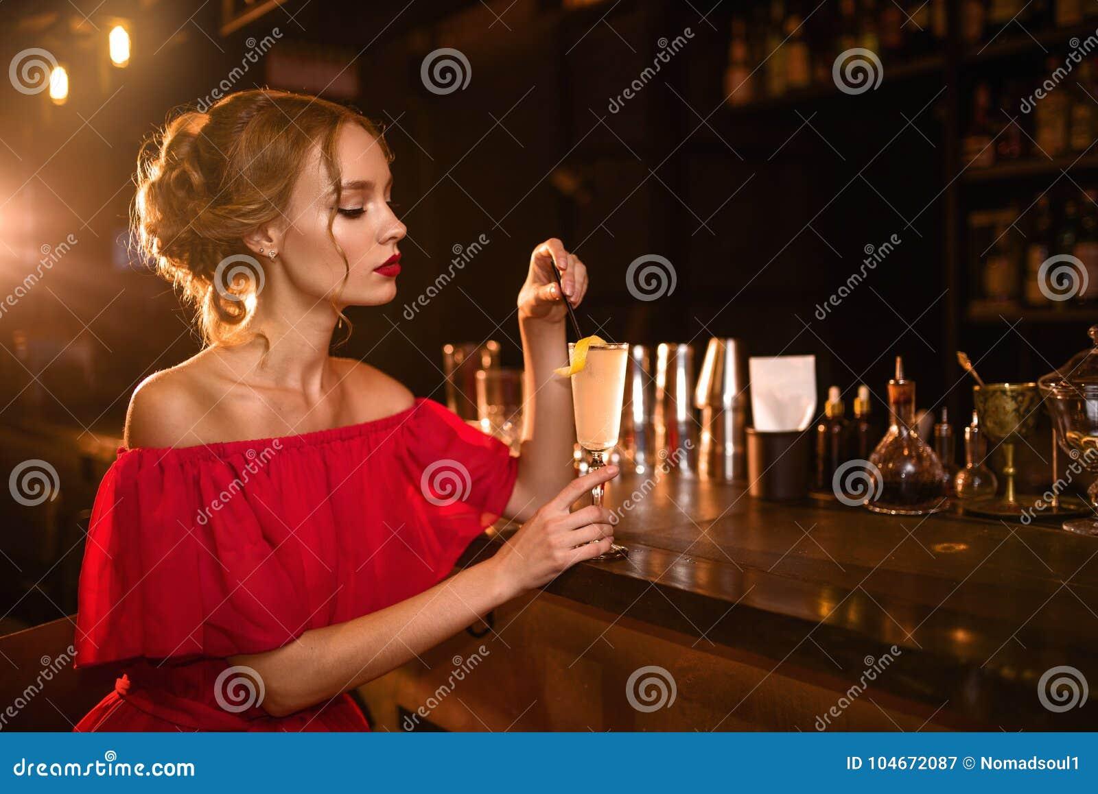 A mulher no vestido vermelho bebe o cocktail no contador da barra