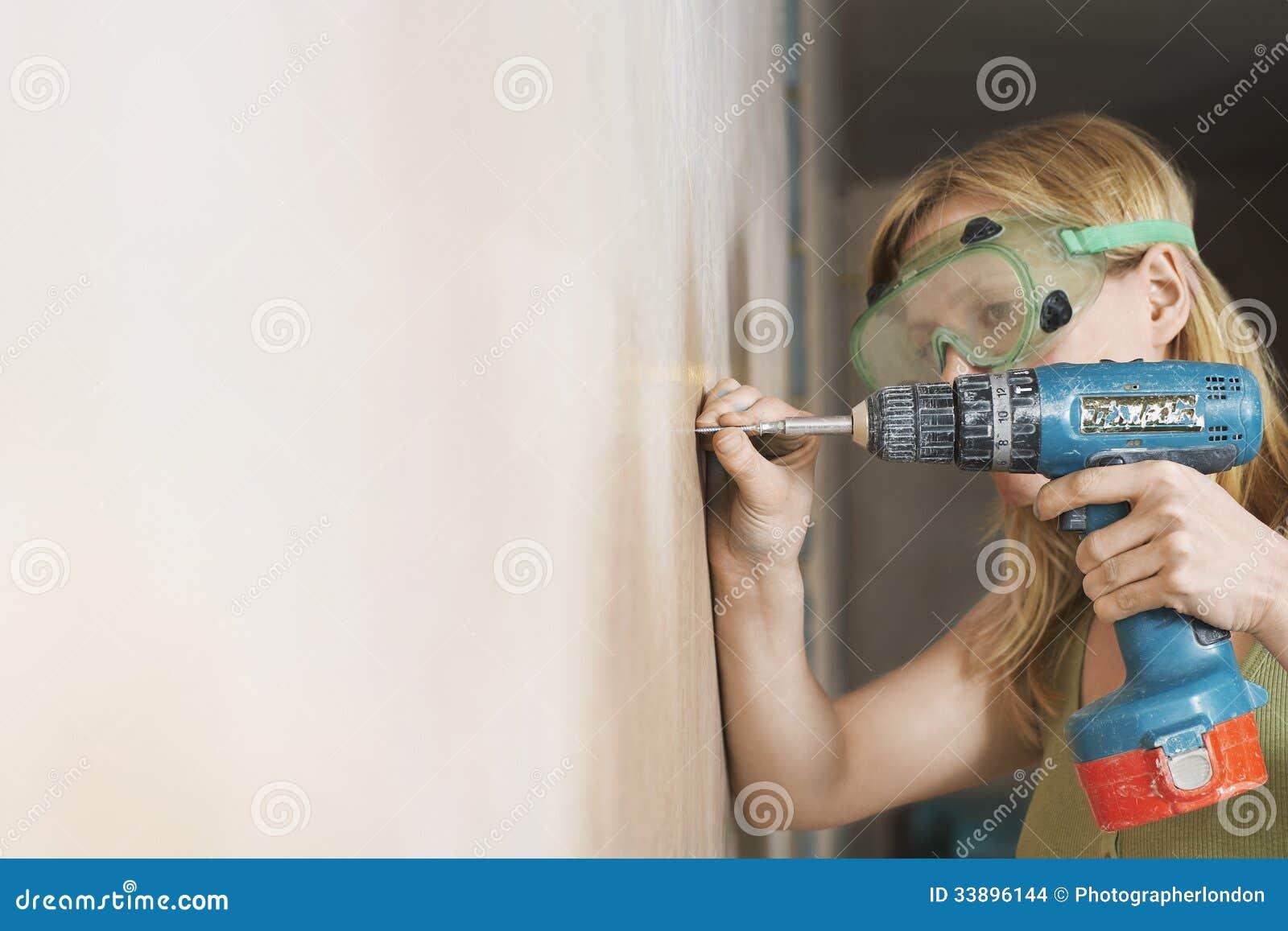 Mulher nos óculos de proteção protetores que furam a parede