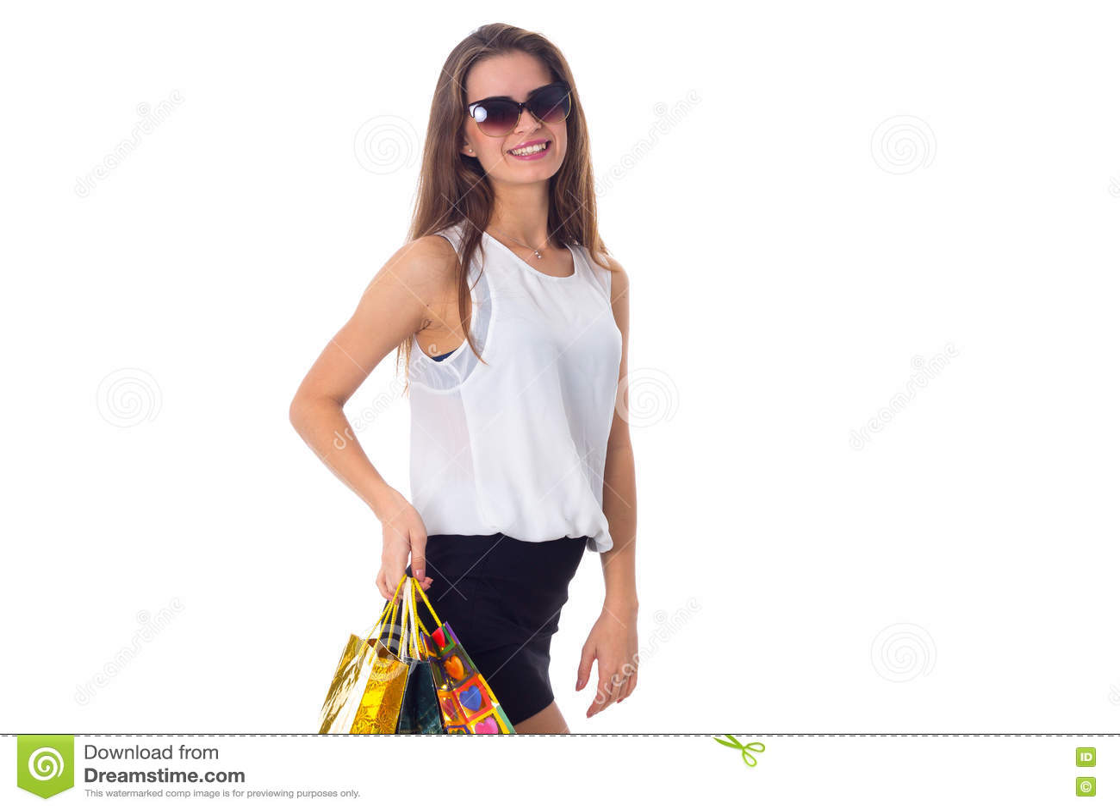 Mulher nos óculos de sol com sacos de compras