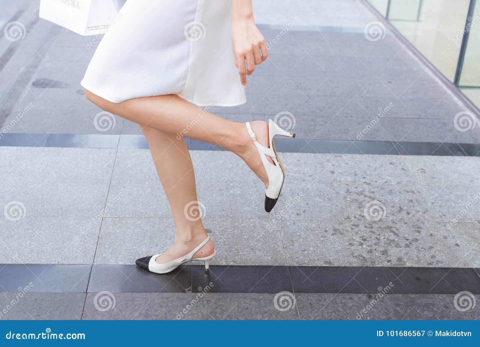 A mulher nos saltos altos tem as dificuldades a andar em suas sapatas