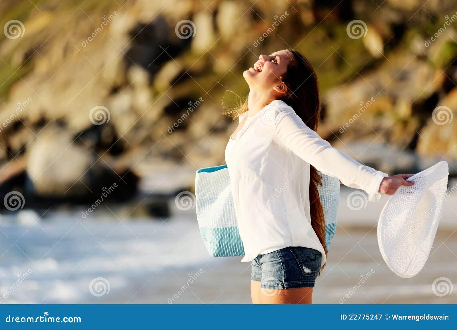 A mulher nova abre seus braços aos arredors