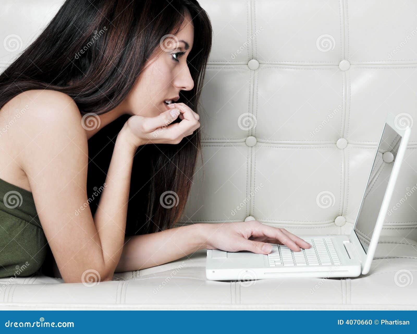 Mulher nova atrativa que usa o portátil em casa