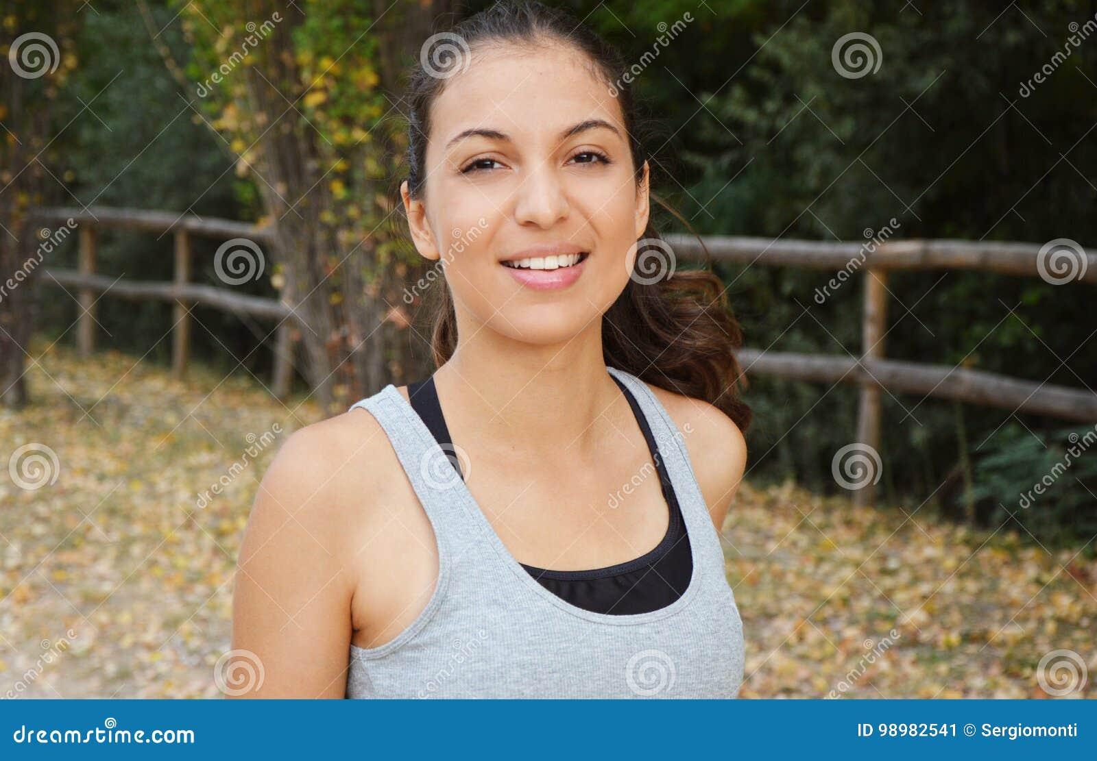 Mulher nova bonita da aptidão que corre no parque Menina de sorriso que treina fora