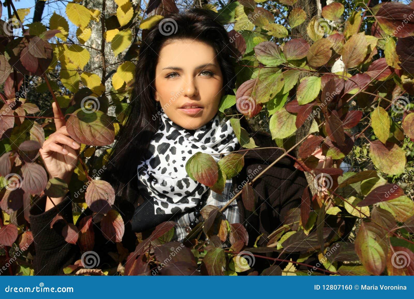 Mulher nova bonita que está entre as folhas