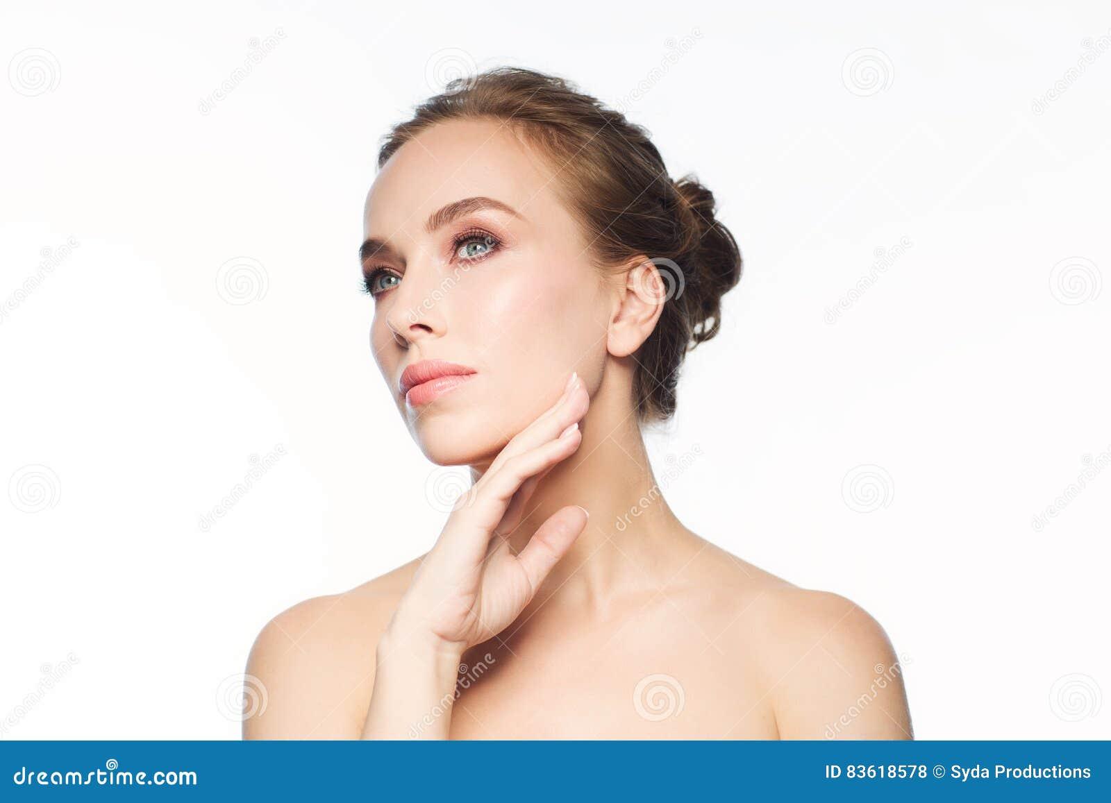 Mulher nova bonita que toca em sua face