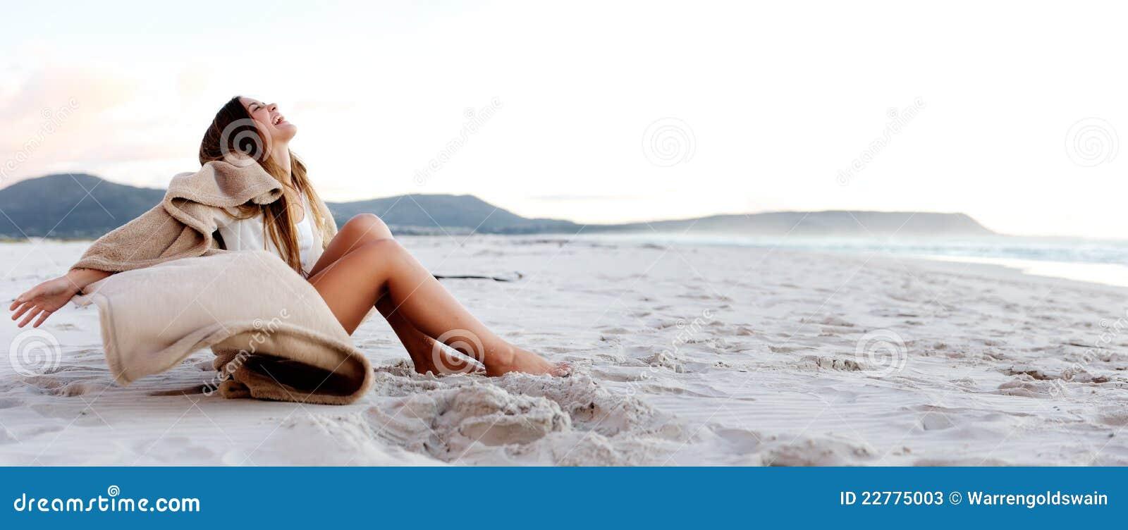 A mulher nova bonita relaxa na praia