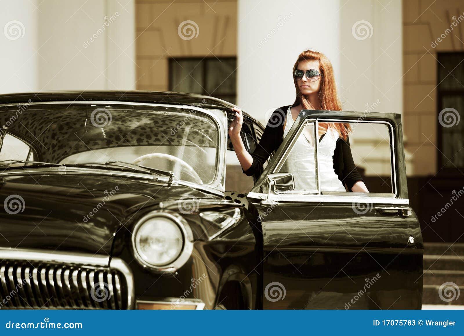 Mulher nova com um carro retro.
