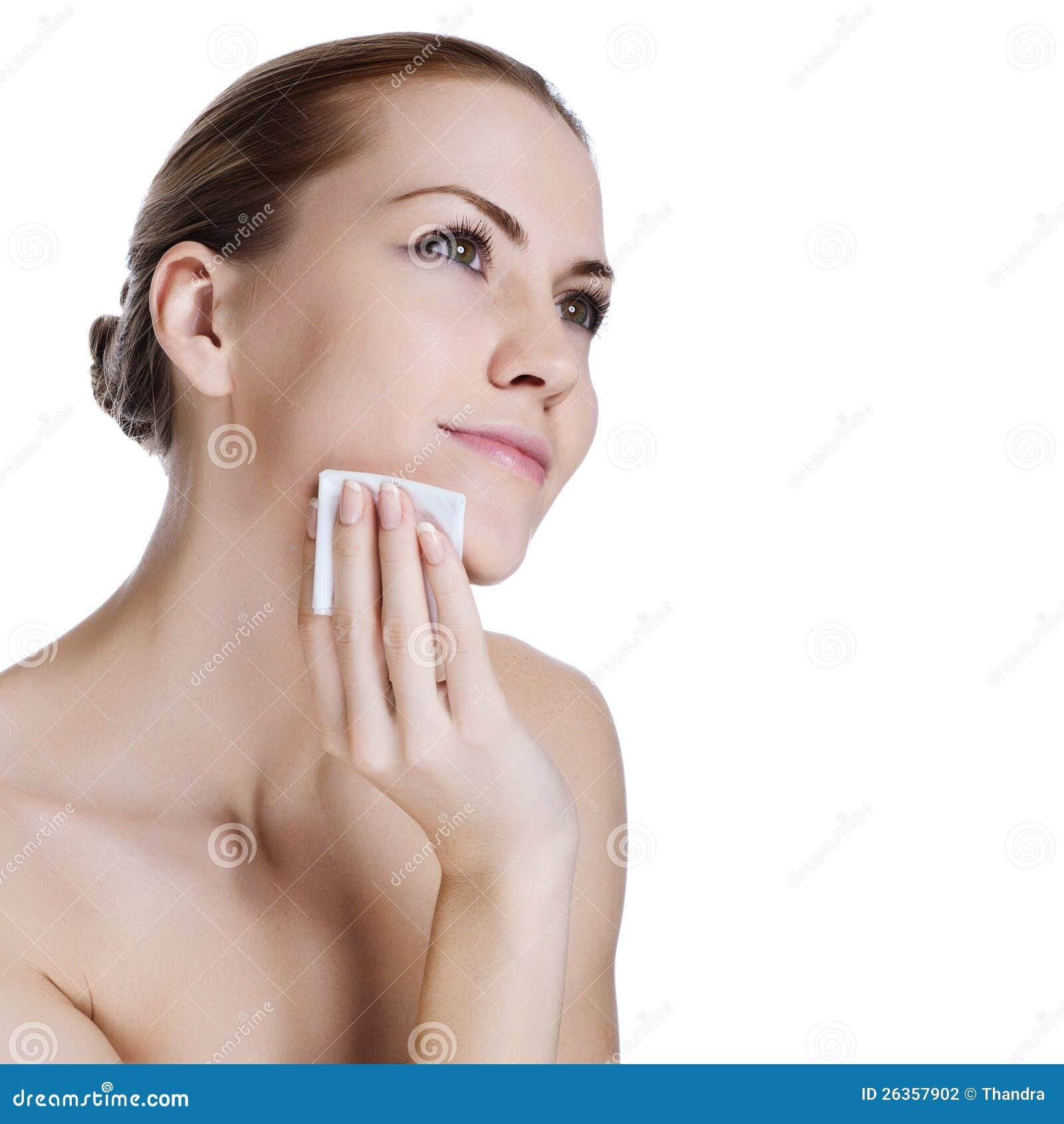 Mulher nova da beleza que aplica a fundação da face