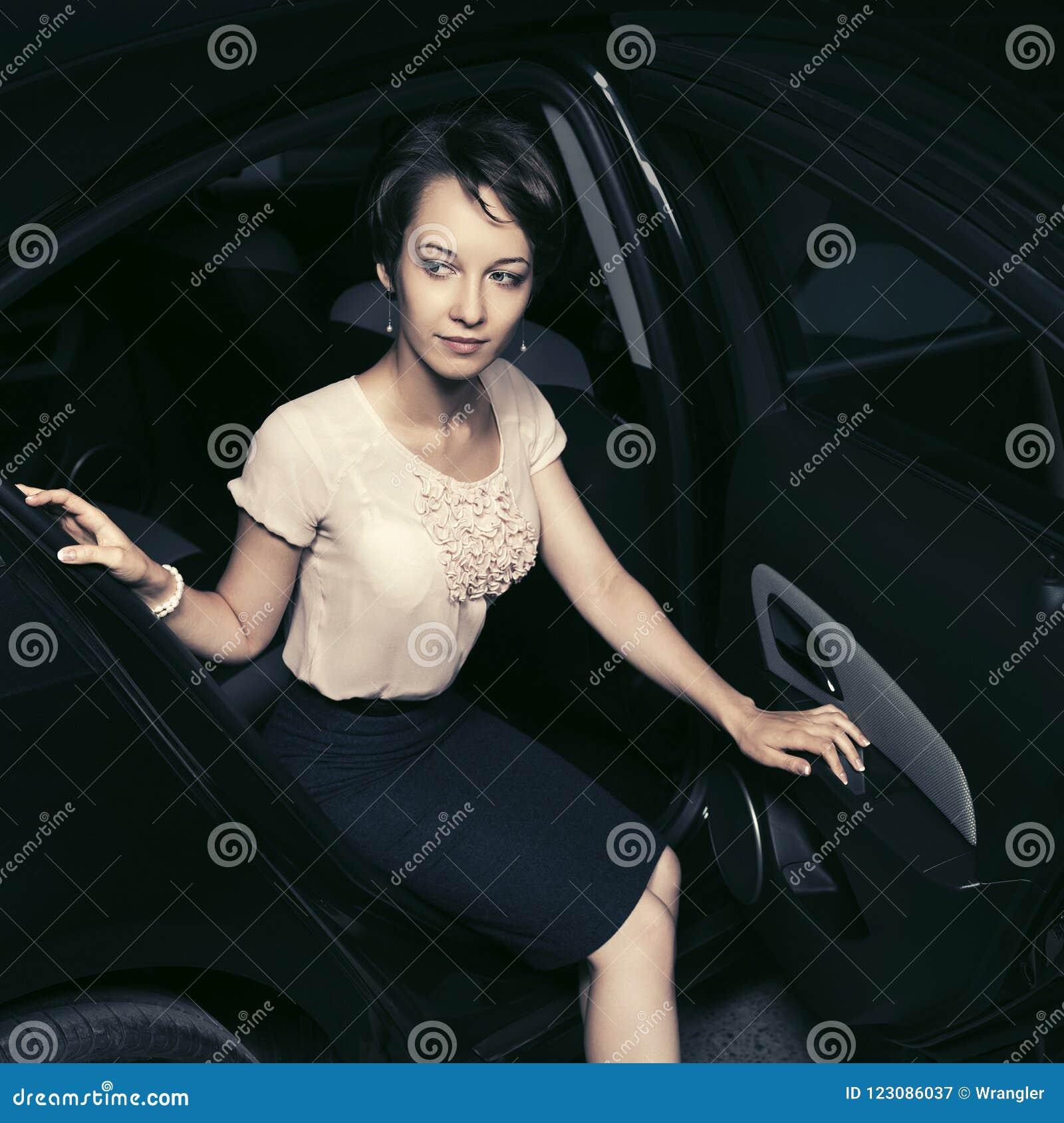 Mulher nova da forma na blusa branca e na saia preta que sentam-se no carro