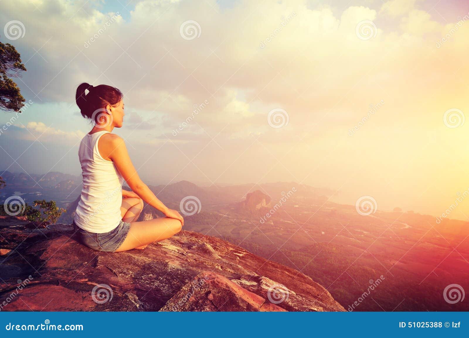 Mulher nova da ioga no nascer do sol