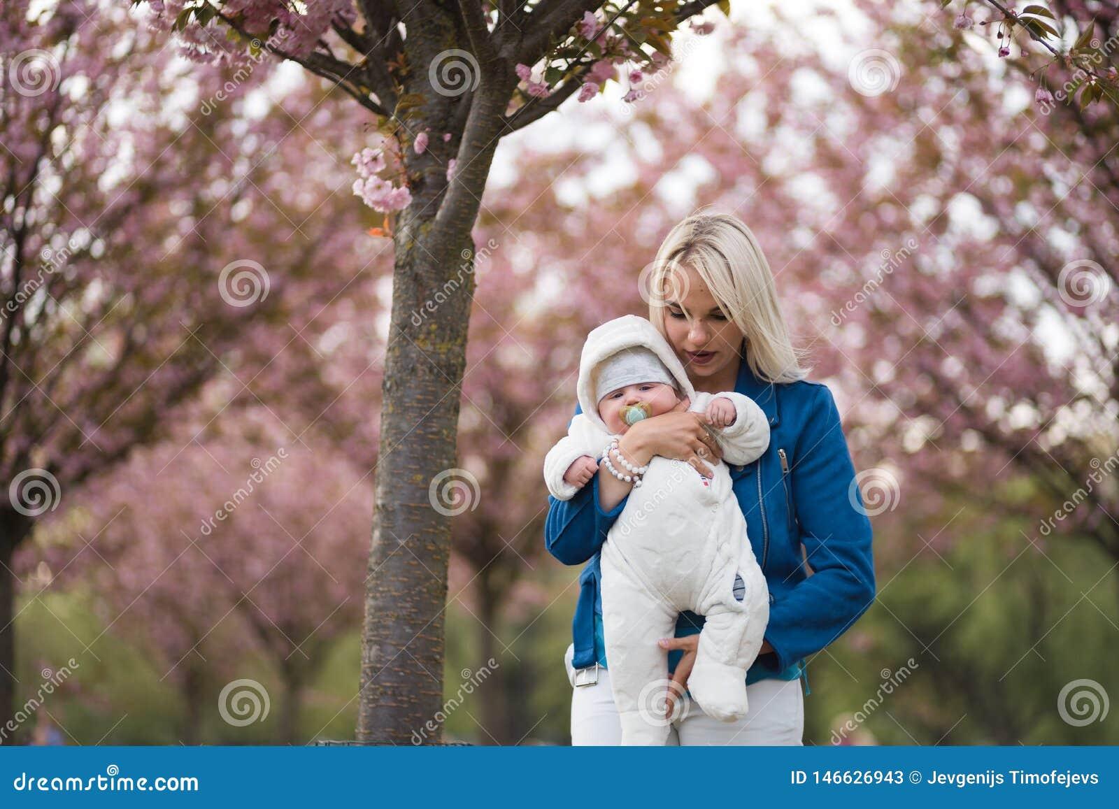Mulher nova da m?e que aprecia o tempo livre com sua crian?a do beb? - crian?a branca caucasiano com a m?o de um pai vis?vel -