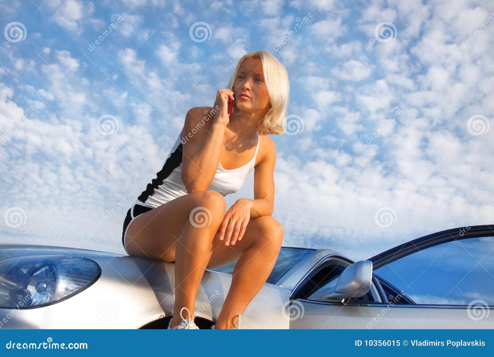 Mulher nova da virada atrativa que senta-se em seu carro