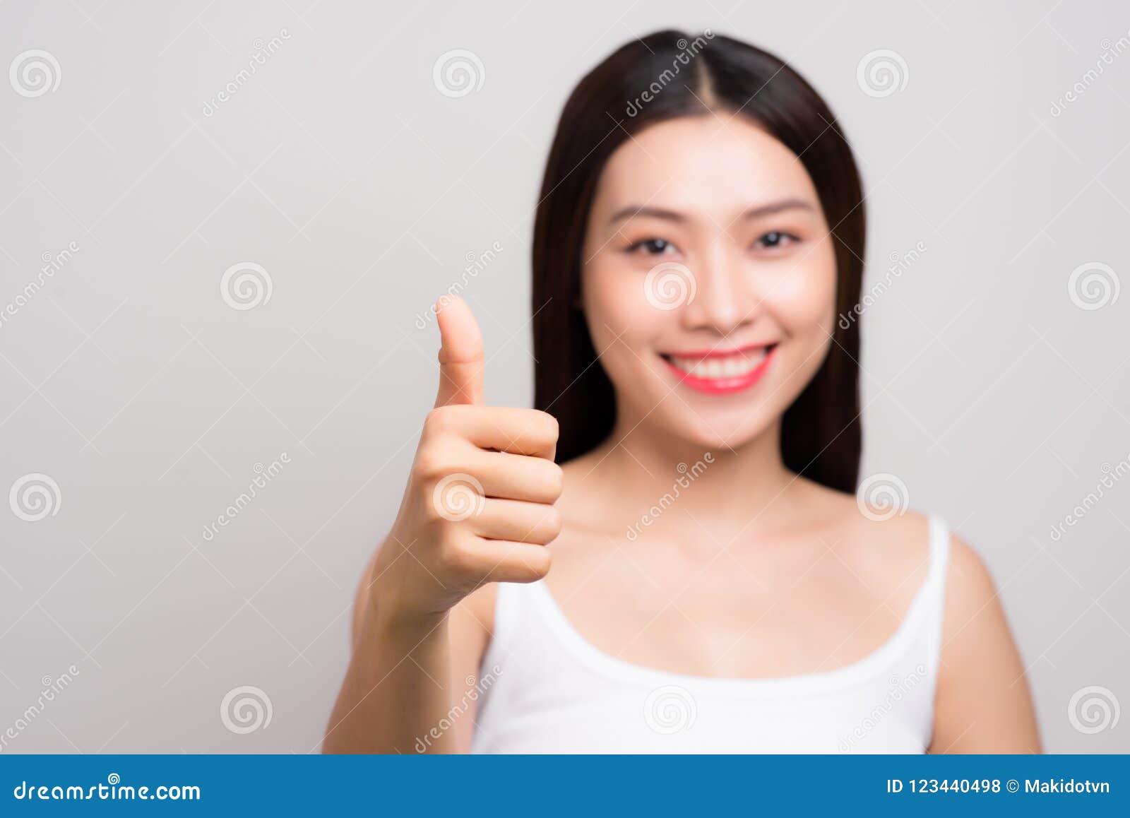 A mulher nova de Ásia com cara do smiley bate acima do gesto, isolado sobre