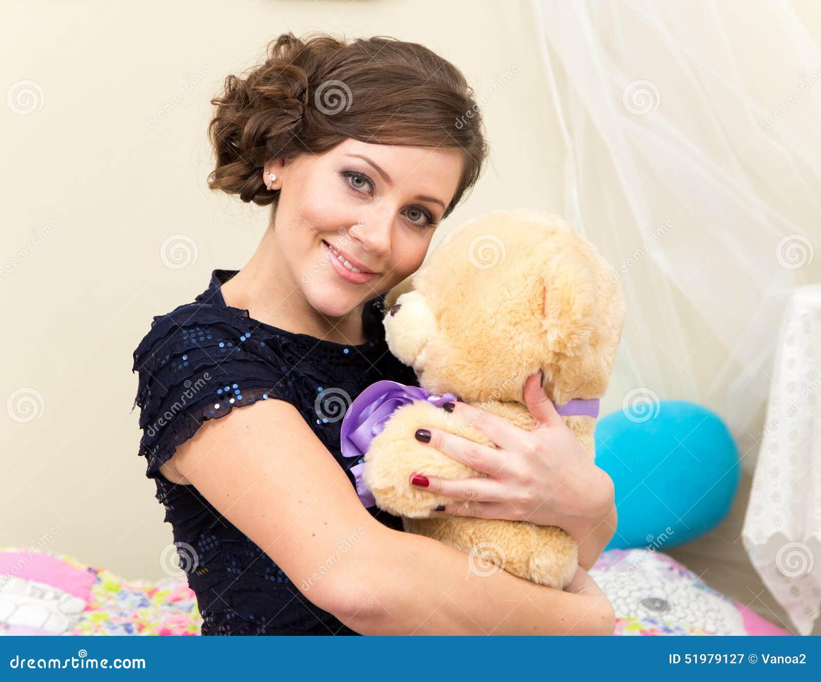 Mulher nova de sorriso com urso da peluche