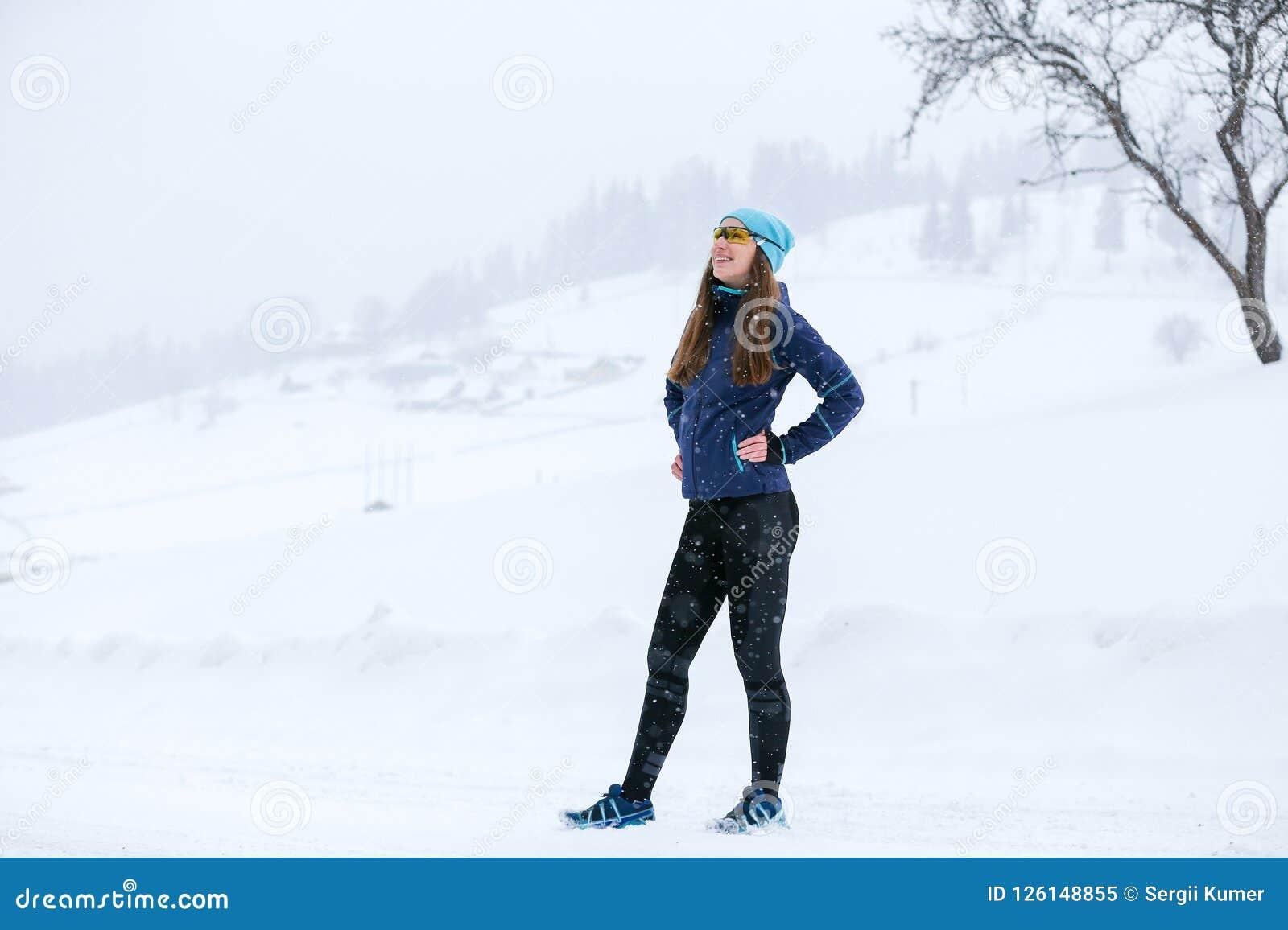 Mulher nova do corredor que está na estrada no inverno